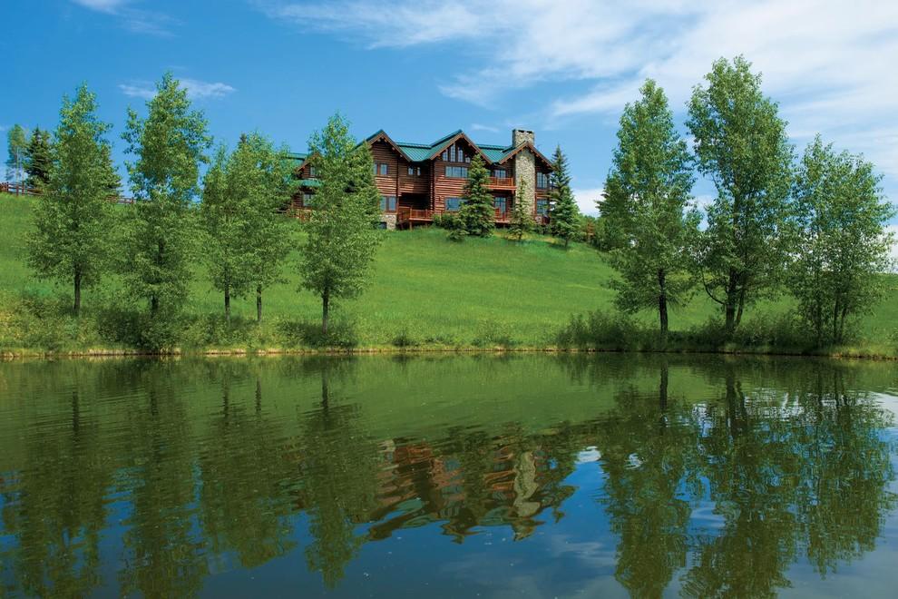 Diseño de fachada de casa marrón, rústica, grande, de tres plantas, con revestimiento de madera, tejado a dos aguas y tejado de metal