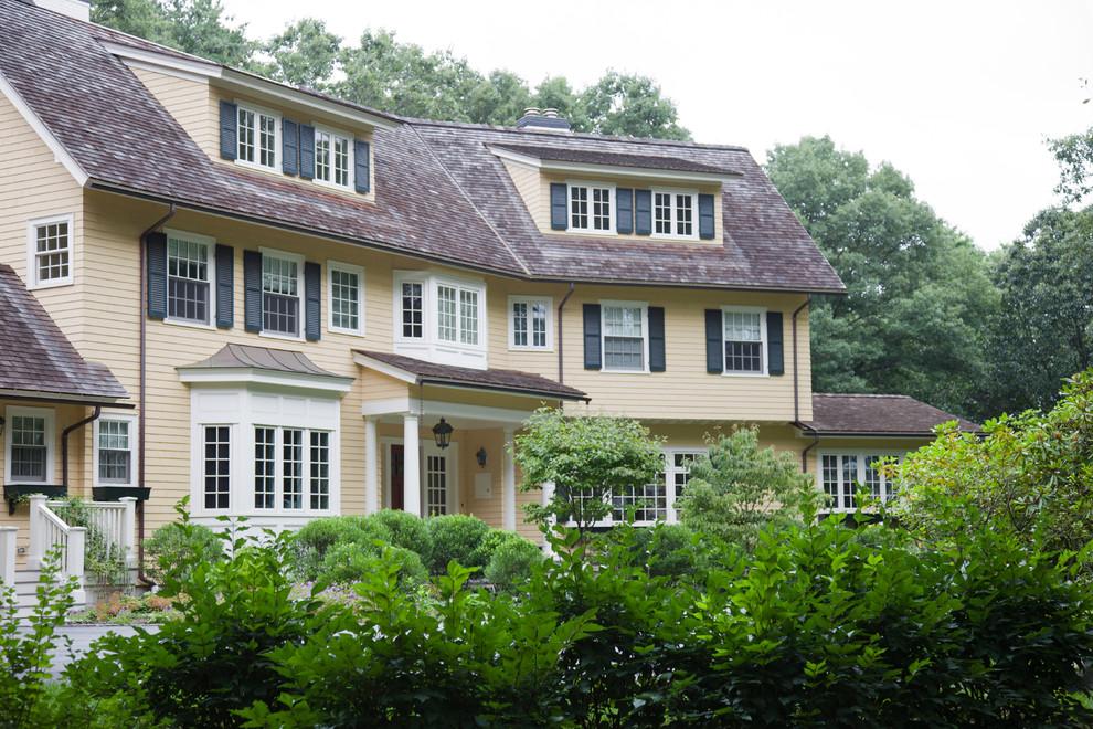 Large elegant yellow three-story wood exterior home photo in Boston