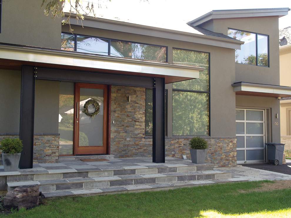 Large modern two-story stone exterior home idea in Toronto