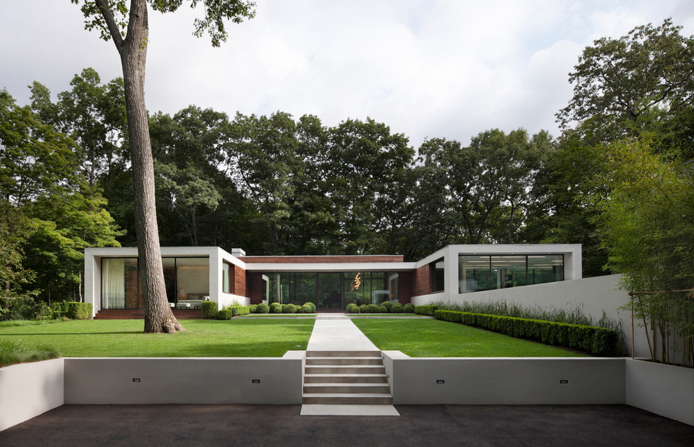 Large modern white one-story stucco flat roof idea in New York