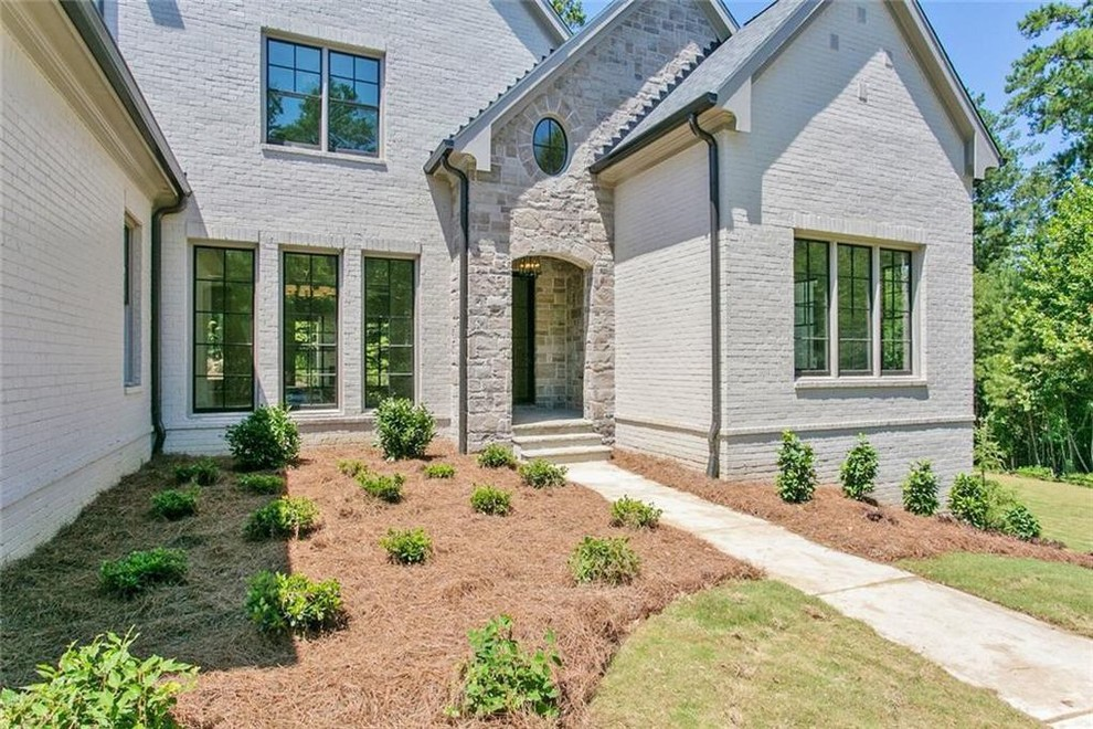 Large transitional gray two-story brick exterior home idea in Atlanta with a shingle roof