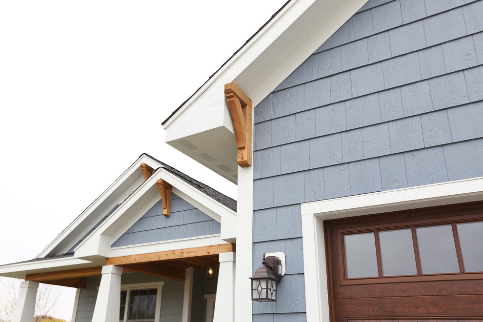 Inspiration for a large craftsman blue two-story wood house exterior remodel in Minneapolis with a hip roof and a shingle roof