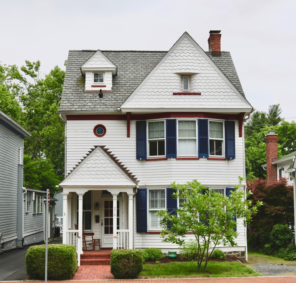 Example of an ornate white two-story exterior home design in DC Metro with a shingle roof