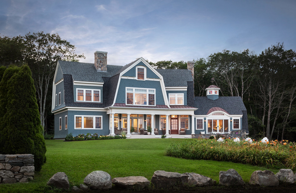 Example of an ornate blue two-story wood exterior home design in Portland Maine with a gambrel roof
