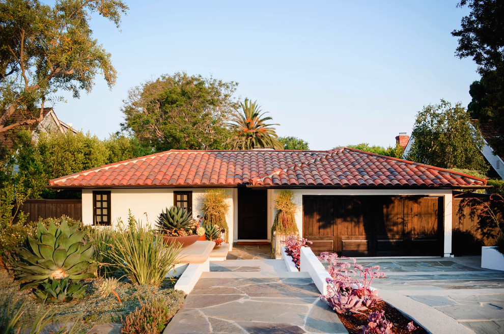 Inspiration for a mid-sized mediterranean white one-story stucco house exterior remodel in Los Angeles with a hip roof and a tile roof