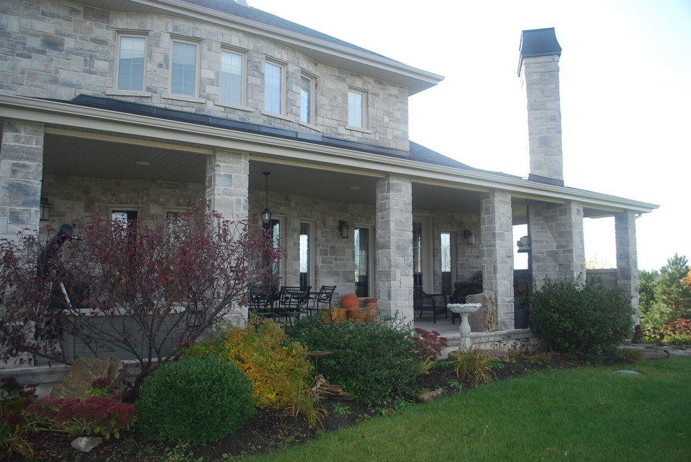 Mid-sized arts and crafts gray two-story stone house exterior photo in Other with a hip roof and a shingle roof