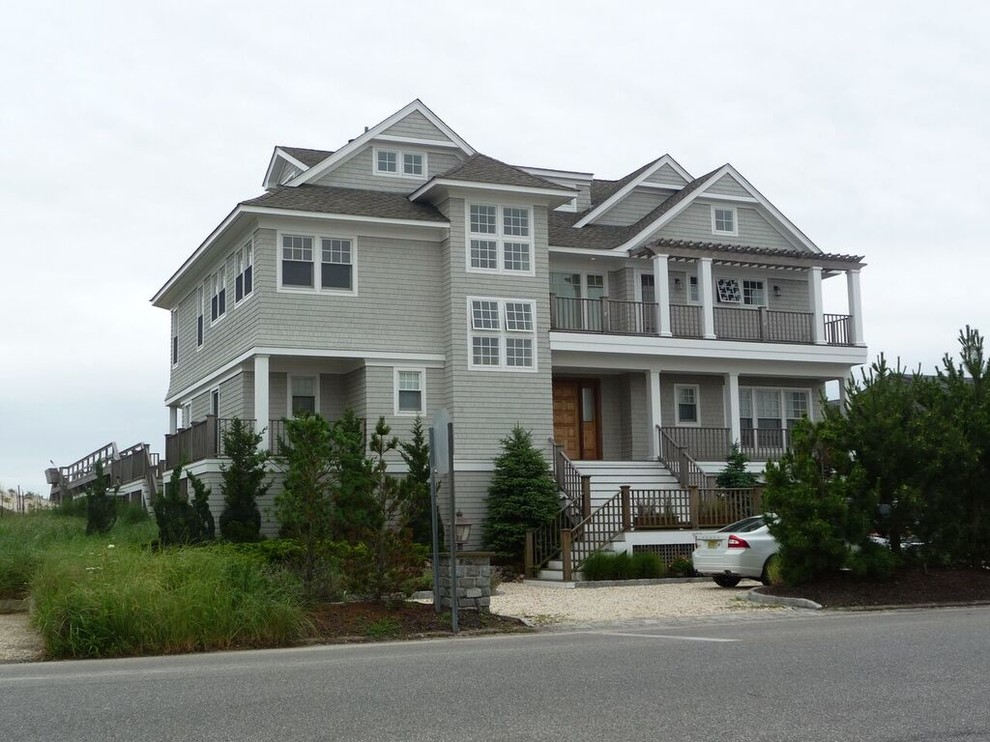 Large beach style gray two-story vinyl gable roof photo in New York