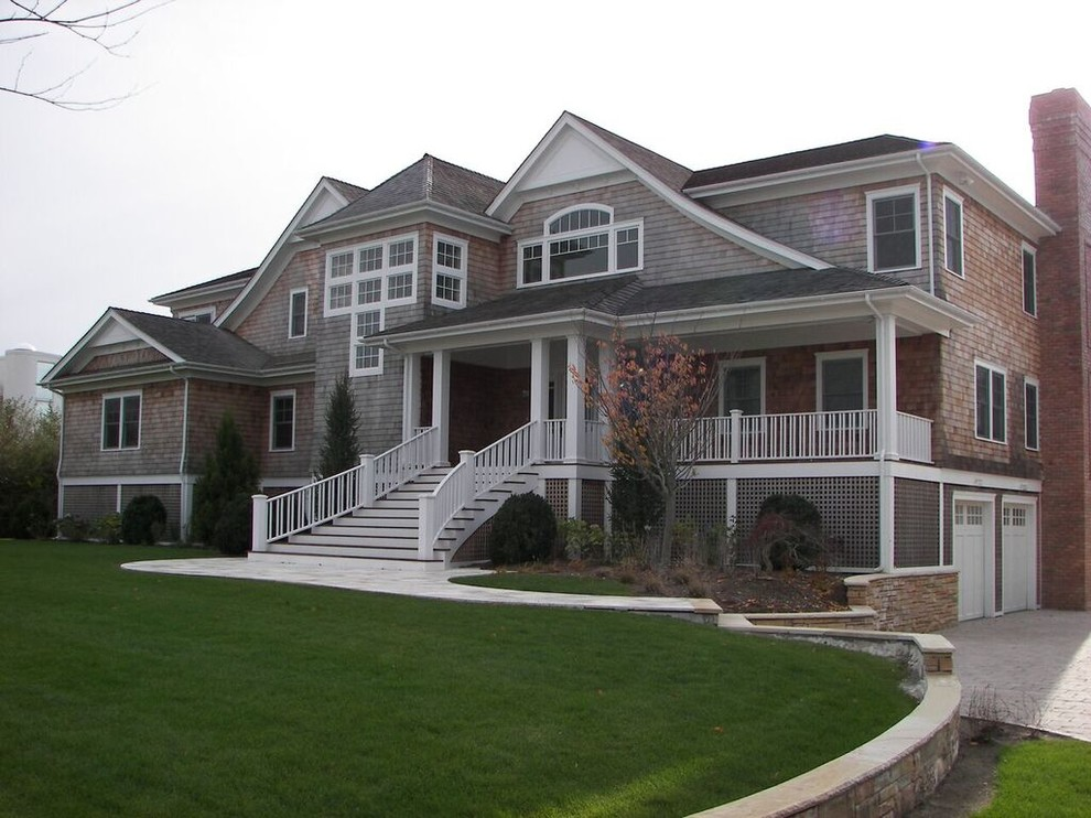 Example of a large classic beige two-story wood gable roof design in New York