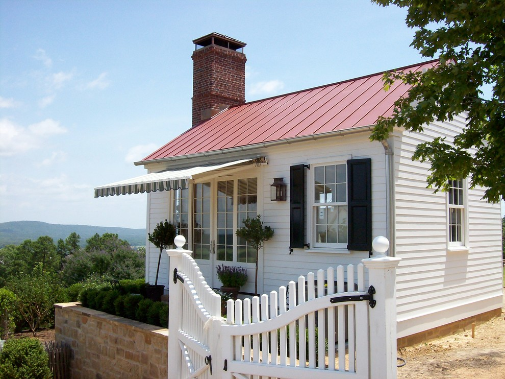Example of a small classic white one-story wood exterior home design in Little Rock with a red roof