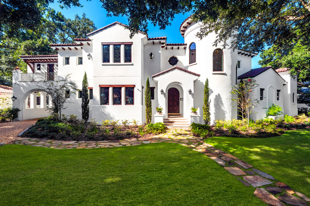 Inspiration for a large mediterranean white two-story stucco house exterior remodel in Tampa with a hip roof, a tile roof and a red roof
