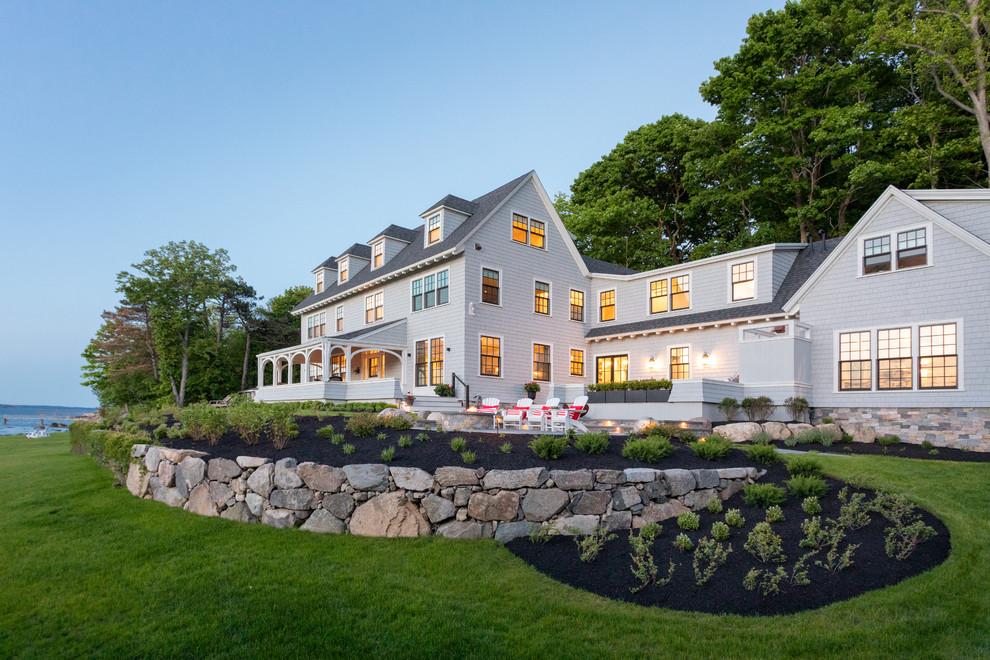 Ejemplo de fachada de casa gris, costera, extra grande, de tres plantas, con revestimiento de madera