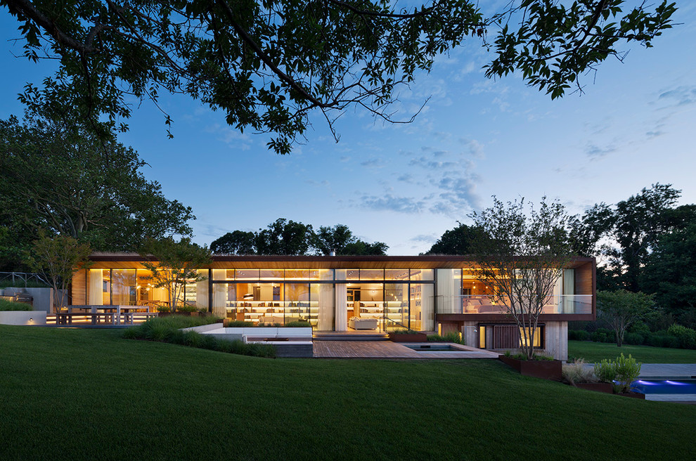 Inspiration for a large contemporary one-story glass exterior home remodel in New York