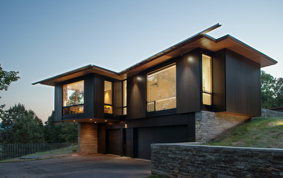 Example of a minimalist black two-story wood house exterior design in Charlotte with a shed roof