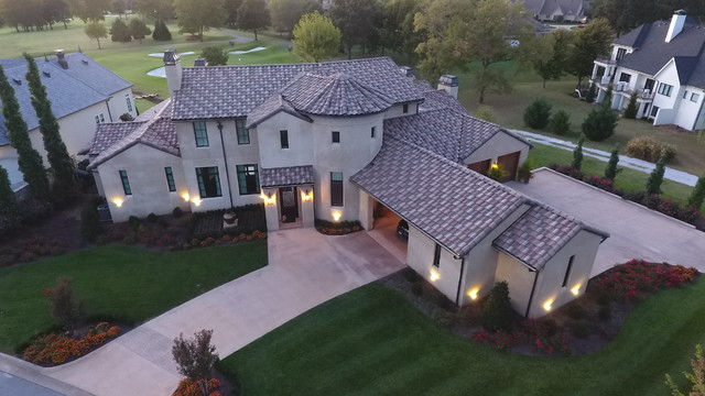 Large tuscan gray two-story stucco house exterior photo in Other with a hip roof and a tile roof