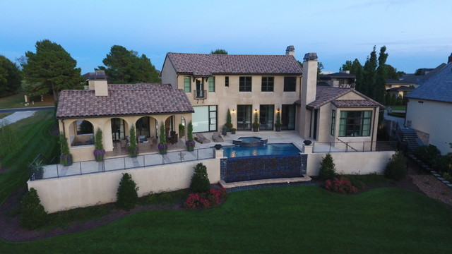 Large tuscan beige two-story stucco exterior home photo in Other with a tile roof