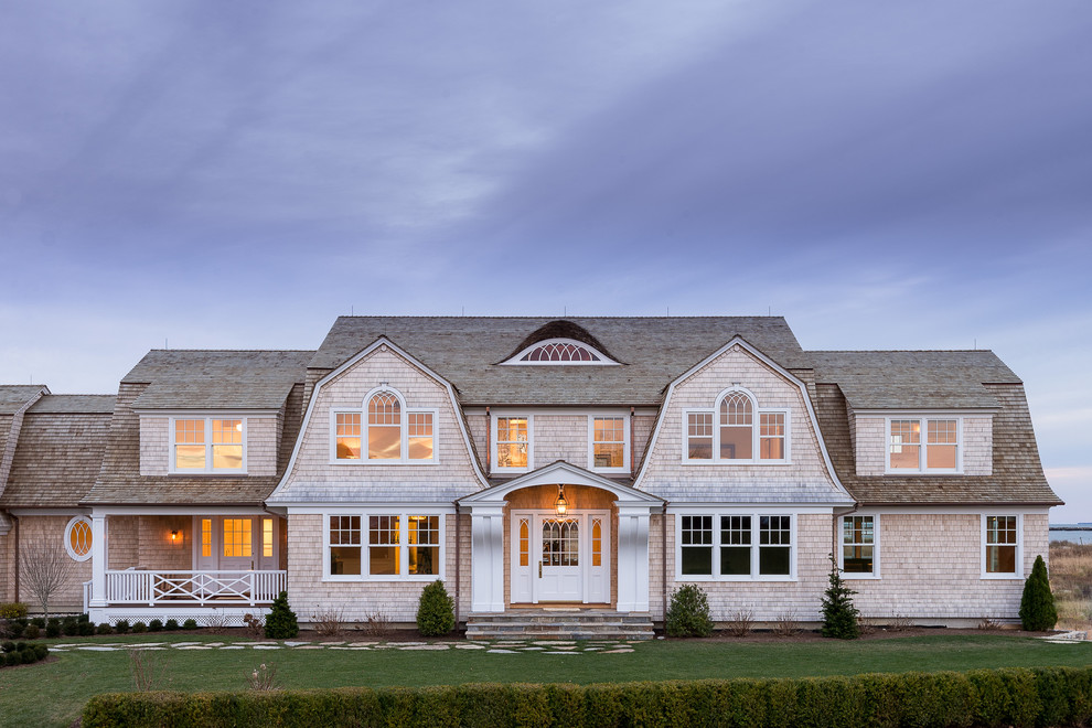 Huge coastal beige two-story wood house exterior idea in Los Angeles with a gambrel roof and a shingle roof
