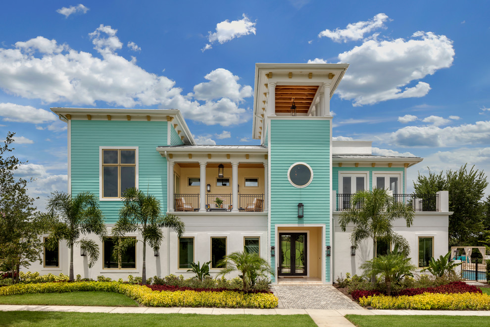 Coastal multicolored two-story mixed siding house exterior idea in Orlando with a hip roof