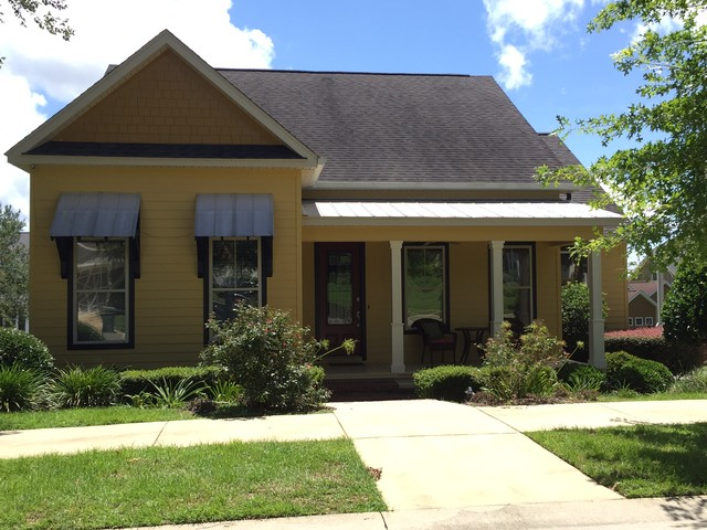 Inspiration for a mid-sized transitional yellow one-story vinyl exterior home remodel in Miami with a shingle roof