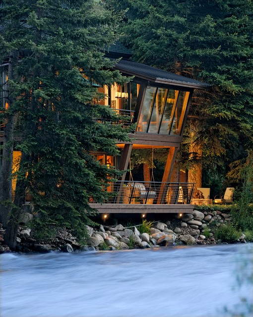 River House Glows Like A Lantern In The Woods Rustic Exterior