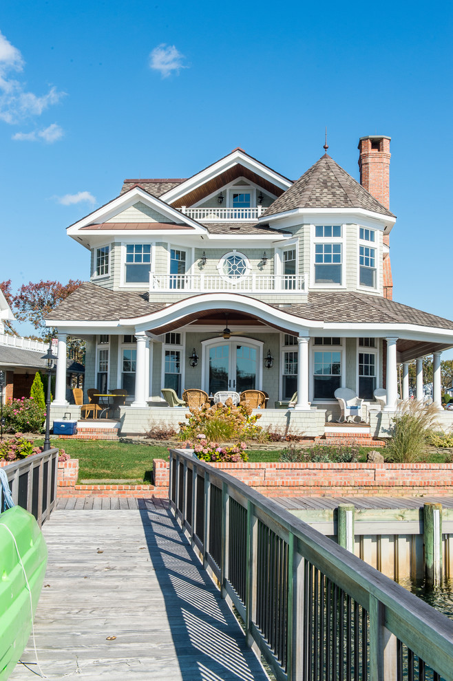 Inspiration for a large victorian green three-story wood gable roof remodel in New York