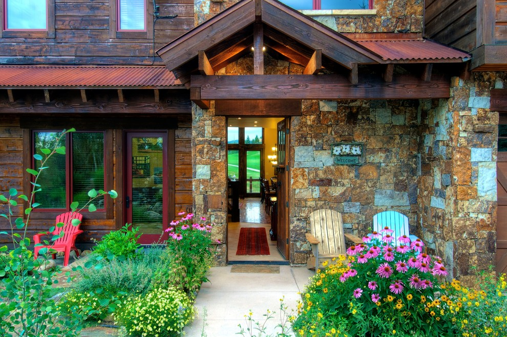 Large elegant brown three-story stone gable roof photo in Denver