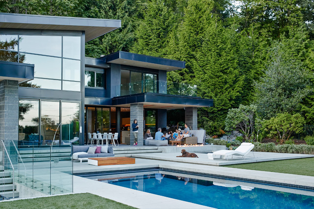 Large contemporary two-story glass exterior home idea in Vancouver with a shed roof
