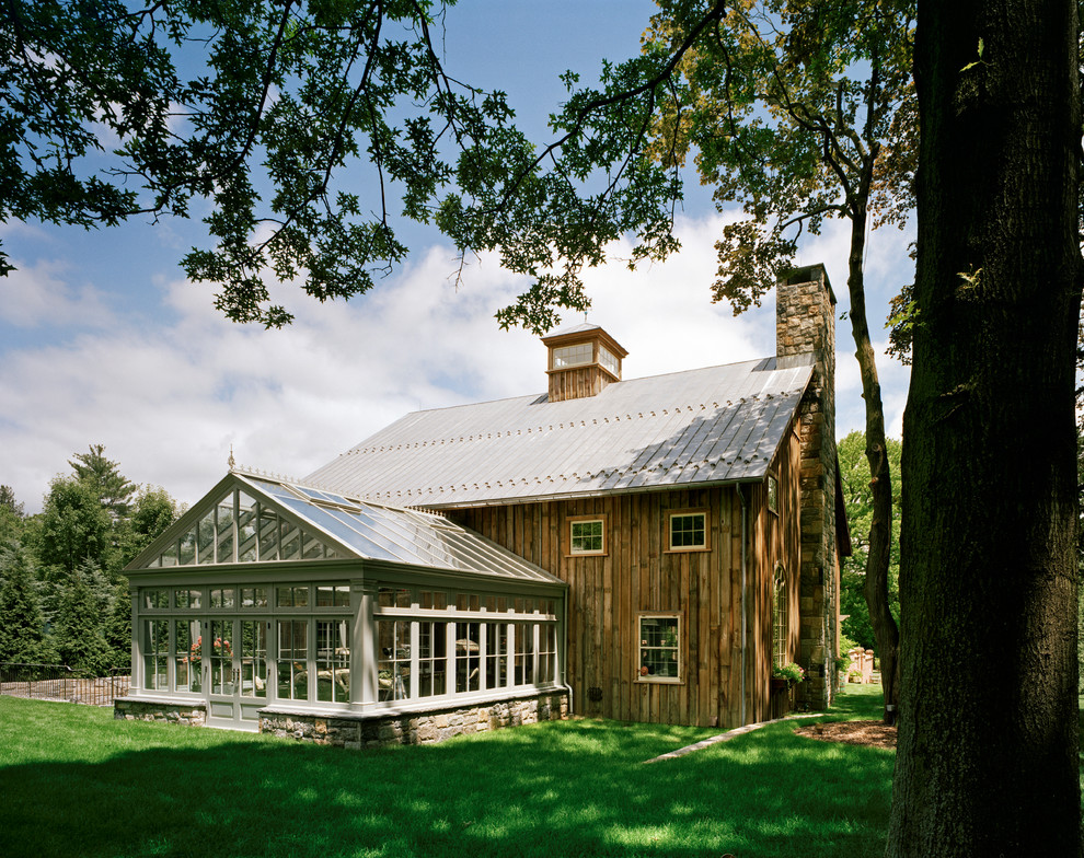 Inspiration for a large country brown two-story wood gable roof remodel in New York