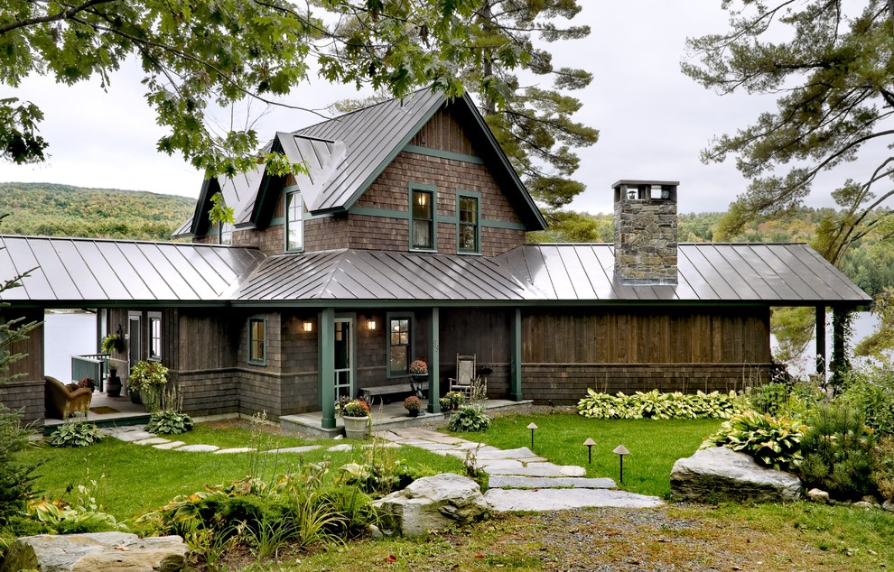 Example of a mountain style wood exterior home design in Burlington with a metal roof