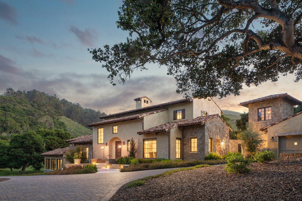 Large mediterranean beige two-story stucco exterior home idea in Orange County with a tile roof