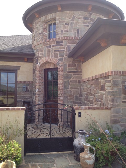 Example of a tuscan beige mixed siding exterior home design in Austin