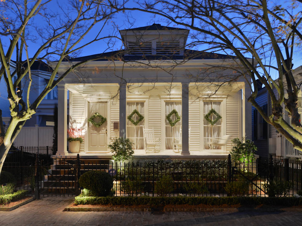 Inspiration for a mid-sized timeless white one-story wood exterior home remodel in New Orleans with a hip roof