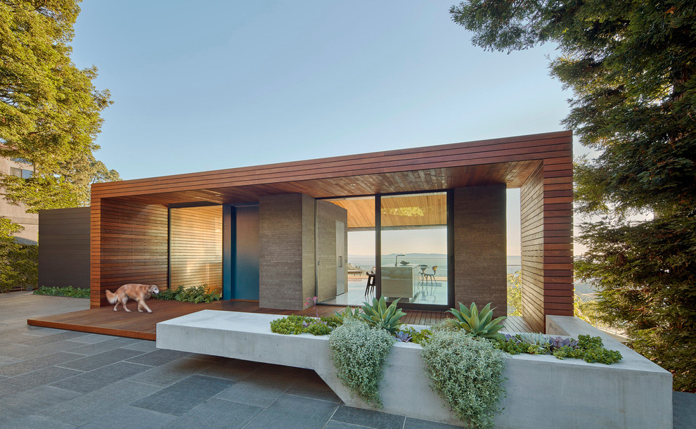 Inspiration for a large modern brown one-story wood flat roof remodel in Orange County