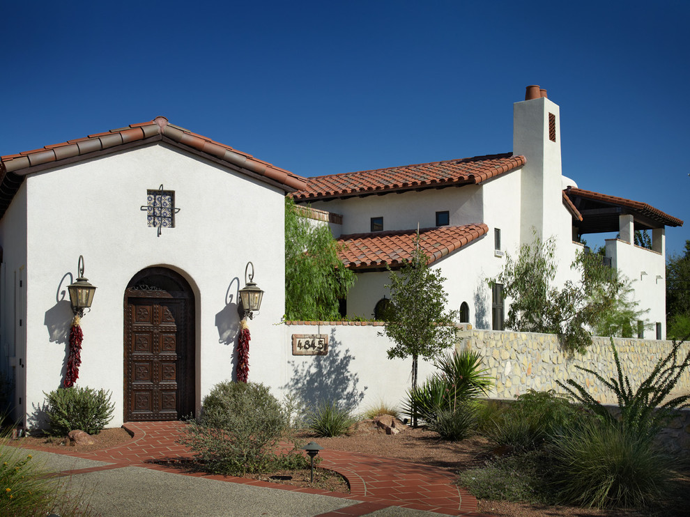 Example of a tuscan two-story exterior home design in Austin with a tile roof