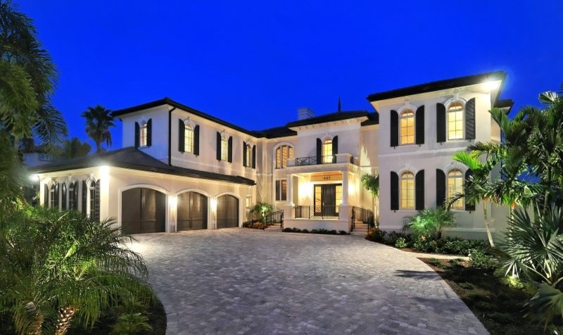 Example of a large tuscan white two-story stucco exterior home design in Tampa with a hip roof