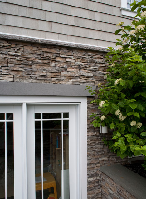 Stacked Stone Exterior And White Window Trimming