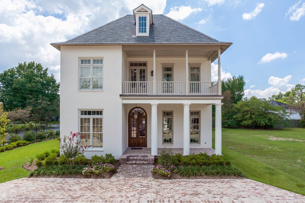 Inspiration for a mid-sized timeless white two-story brick house exterior remodel in New Orleans with a hip roof and a shingle roof