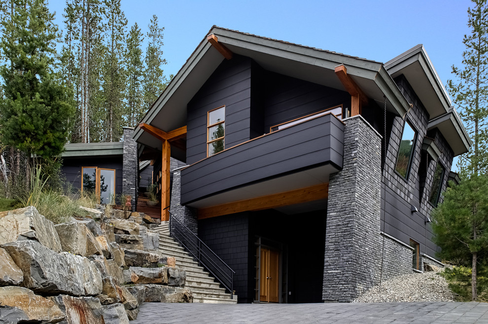 Example of a trendy black two-story exterior home design in Calgary