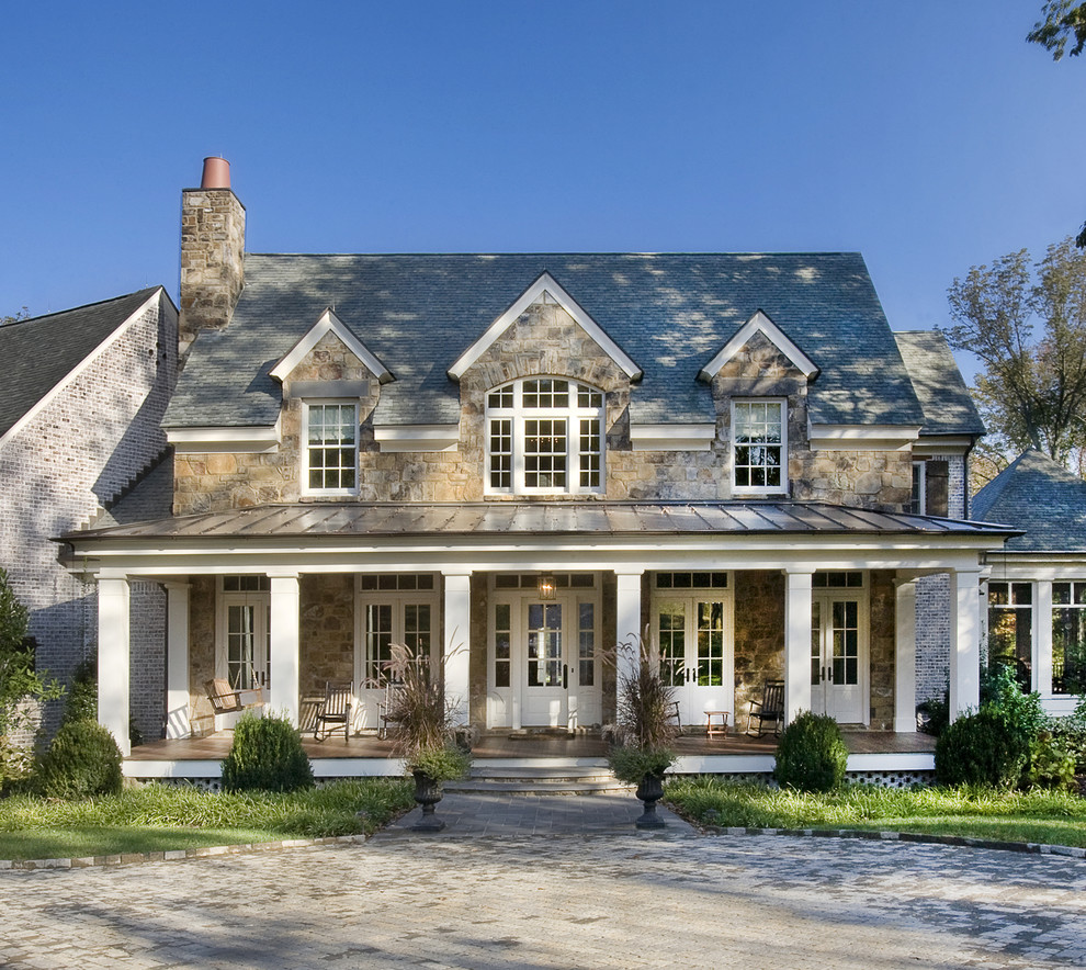 Large traditional brown two-story stone gable roof idea in Nashville with a shingle roof