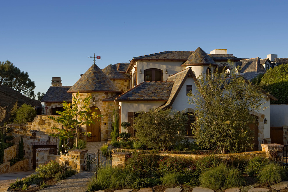 Large traditional white two-story stone exterior home idea in Orange County
