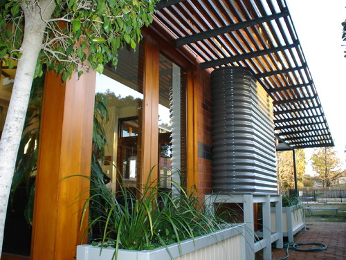 how to conceal a rainwater tank  by installing on the side of the house
