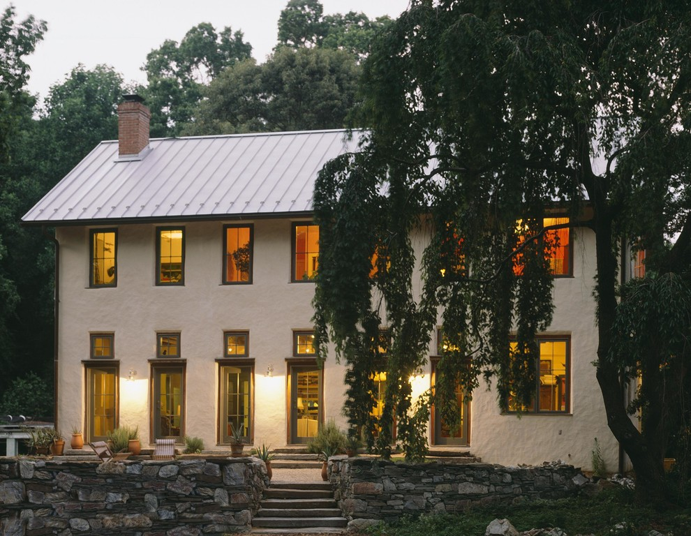 Inspiration for a mid-sized farmhouse beige two-story stucco gable roof remodel in Baltimore with a metal roof
