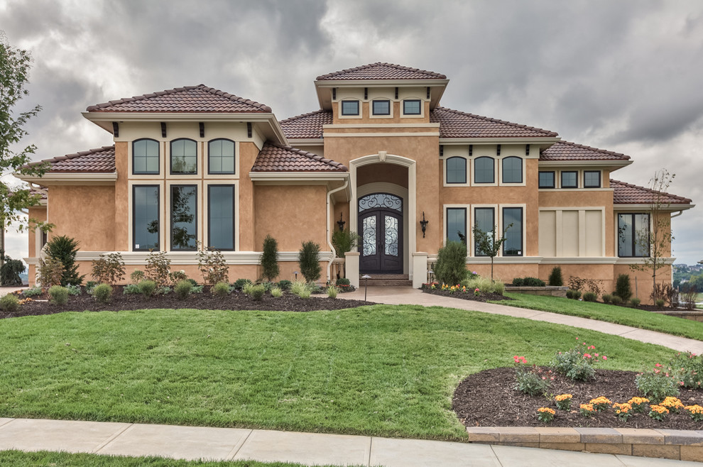 Inspiration for a large mediterranean beige two-story stucco house exterior remodel in Omaha