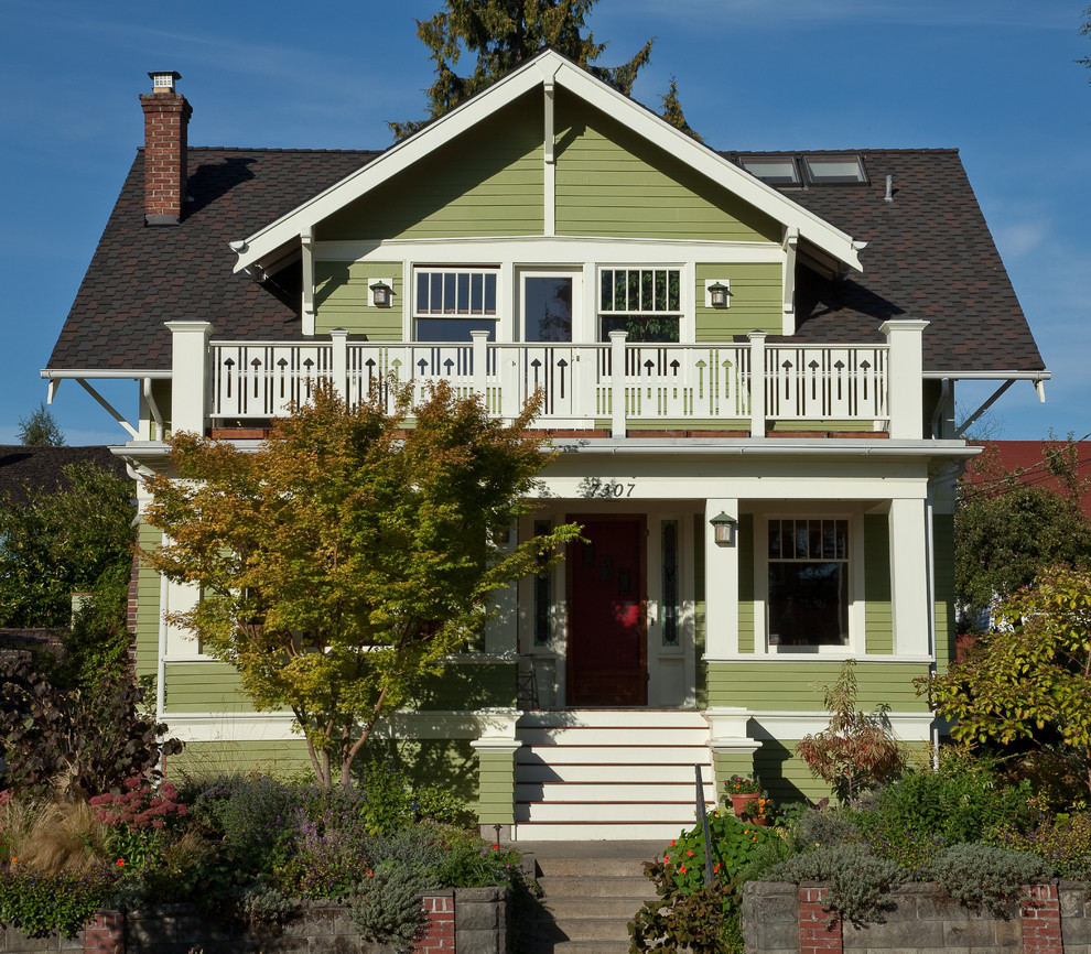 Mid-sized elegant green two-story wood gable roof photo in Seattle