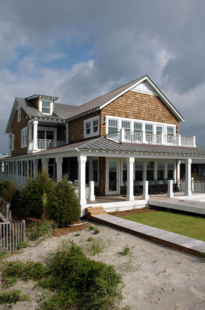 Inspiration for a mid-sized coastal two-story wood gable roof remodel in Wilmington with a metal roof