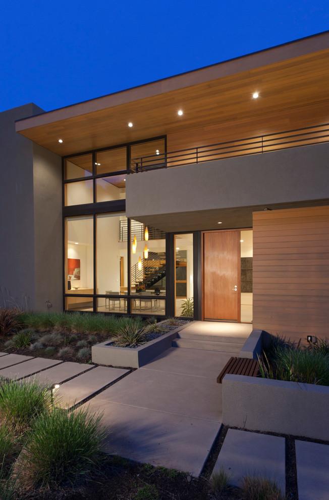 Modelo de fachada moderna, de tamaño medio, de dos plantas, con revestimientos combinados y tejado plano