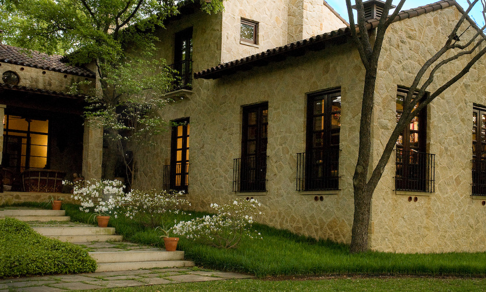 Inspiration for a large mediterranean brown two-story stone exterior home remodel in Dallas with a tile roof