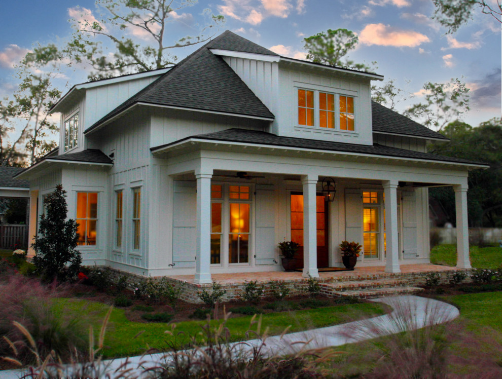 Mid-sized traditional white two-story wood exterior home idea in Other with a clipped gable roof
