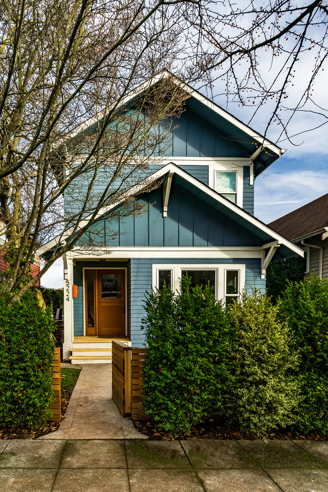 Example of a mid-sized arts and crafts blue two-story concrete fiberboard exterior home design in Seattle with a shingle roof