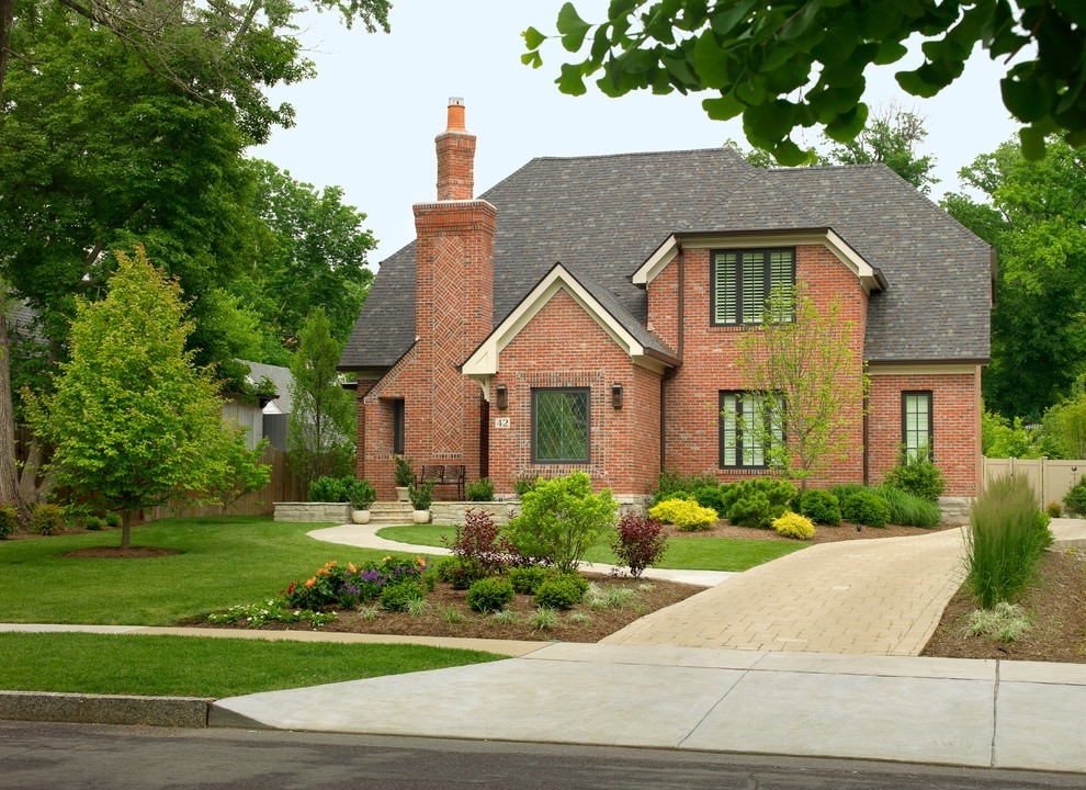Traditional brick exterior home idea in St Louis with a clipped gable roof