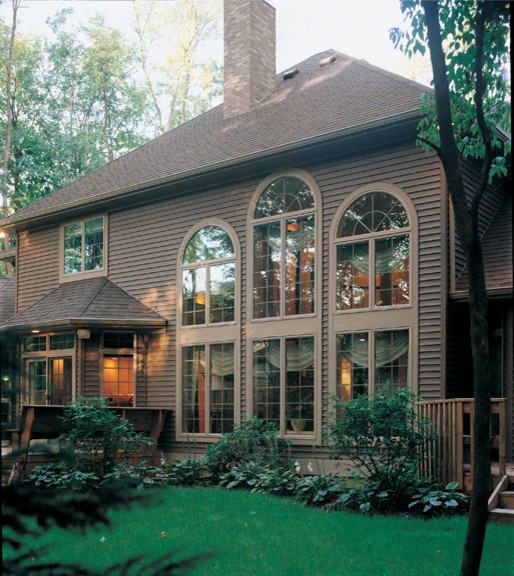 Large elegant brown three-story vinyl exterior home photo in DC Metro with a hip roof
